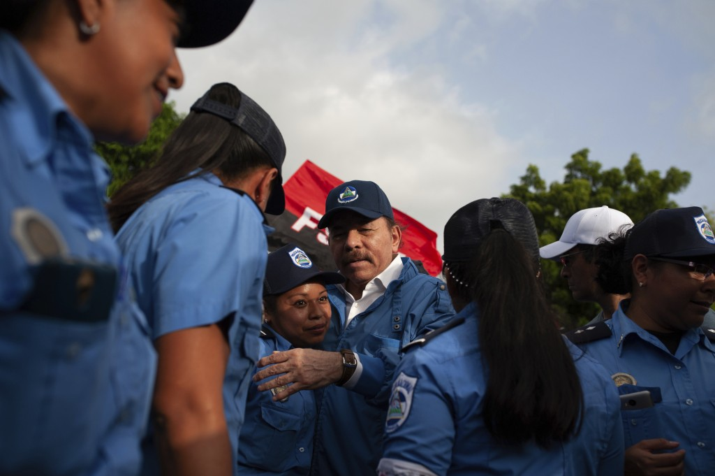 Nicaraguan President Daniel Ortega poses for photos with female police officers after his arrival in Masaya, Nicaragua, Friday, July 13, 2018. Accordi