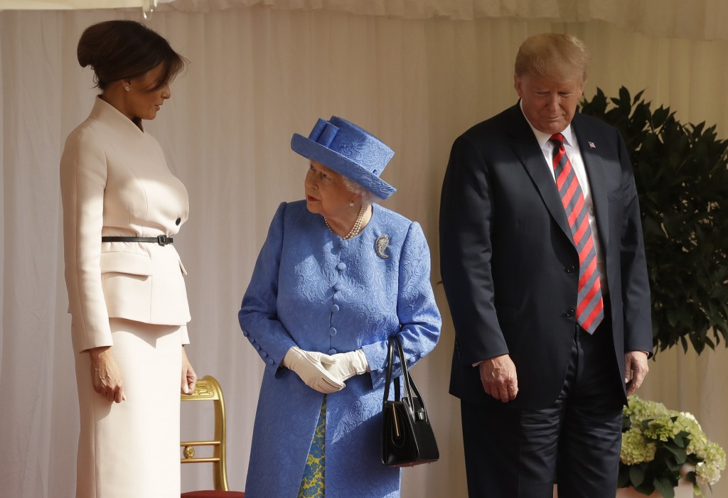 Britain's Queen Elizabeth II speaks to first lady Melania Trump, as U.S. President Donald Trump looks on as they stand on the dais in the Quadrangle o