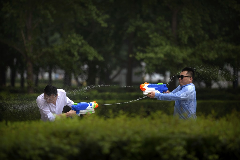 Office workers spray each other with water guns outside their office building in Beijing, Friday, July 13, 2018. Employees in China sometimes put in l