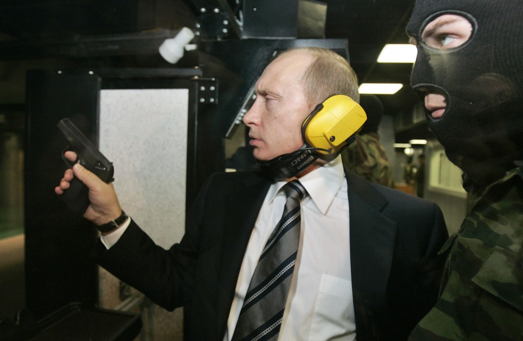 FILE In this file photo taken on Wednesday, Nov. 8, 2006, President Vladimir Putin wears headphones as he tests a pistol in a shooting range as he vis