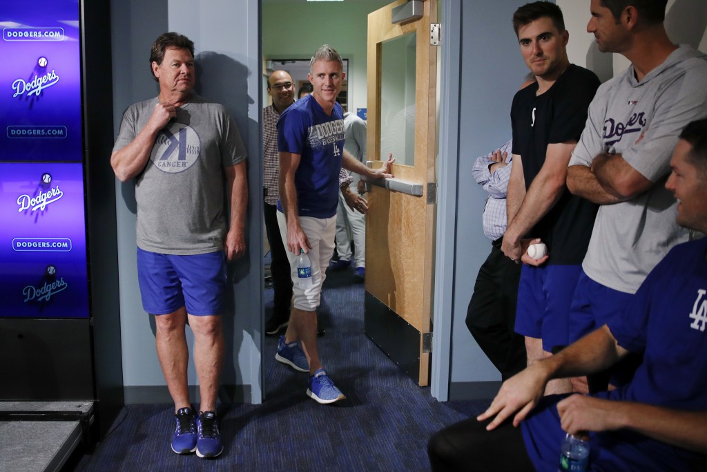 Los Angeles Dodgers infielder Chase Utley, center, walks into an interview room to announce his retirement at the end of the season, Friday, July 13,