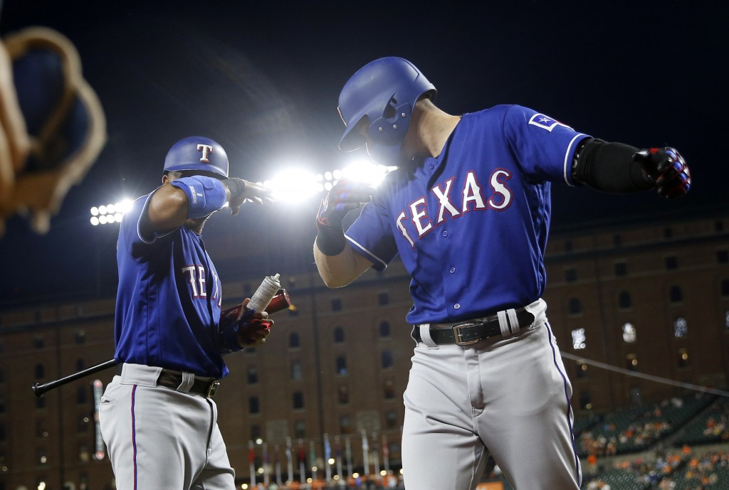 Texas Rangers' Ryan Rua, right, and Elvis Andrus gesture after Rua hit a three-run home run in the seventh inning of a baseball game against the Balti