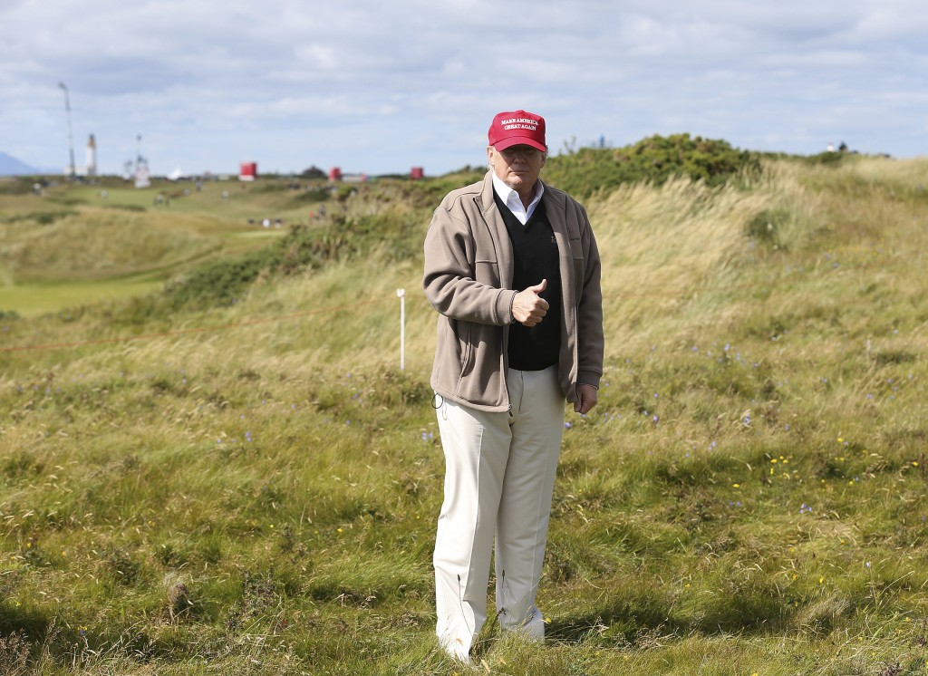 FILE - In this July 30, 2015, then-presidential contender Donald Trump gestures to the media on the 17th fairway on the first day of the Women's Briti