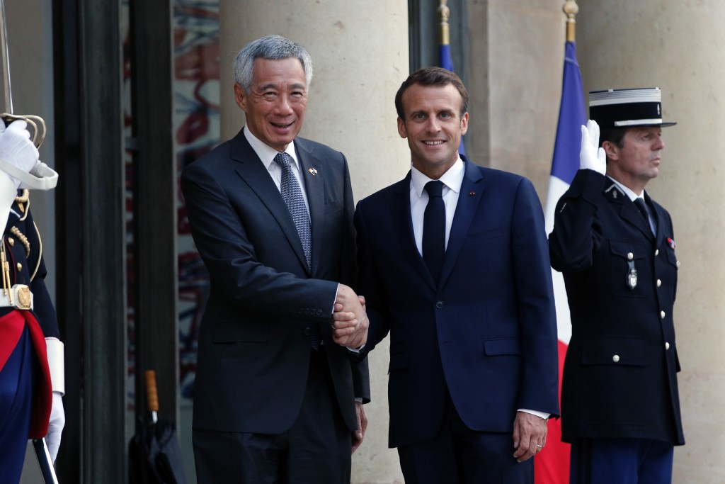 France's President Emmanuel Macron, right, shakes hand with Singapore Prime Minister Lee Hsien Loong, prior to a State dinner, at the Elysee Palace, i
