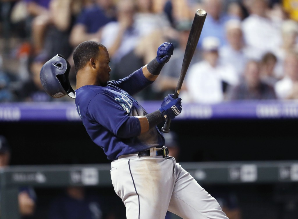 Seattle Mariners' Jean Segura loses his helmet while trying to check his swing on a strikeout against Colorado Rockies relief pitcher Adam Ottavino du