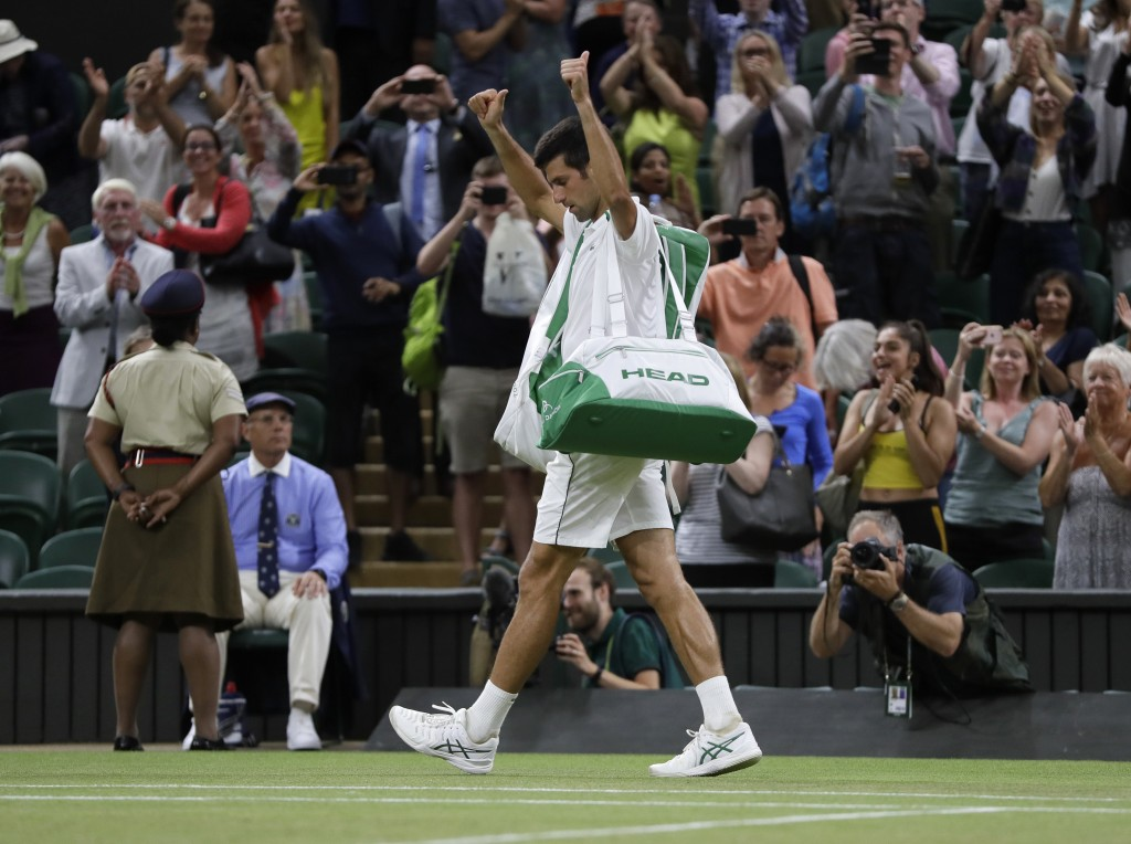 Serbia's Novak Djokovic leaves the court after play was suspended in his men's singles semifinals match against Rafael Nadal of Spain at the Wimbledon