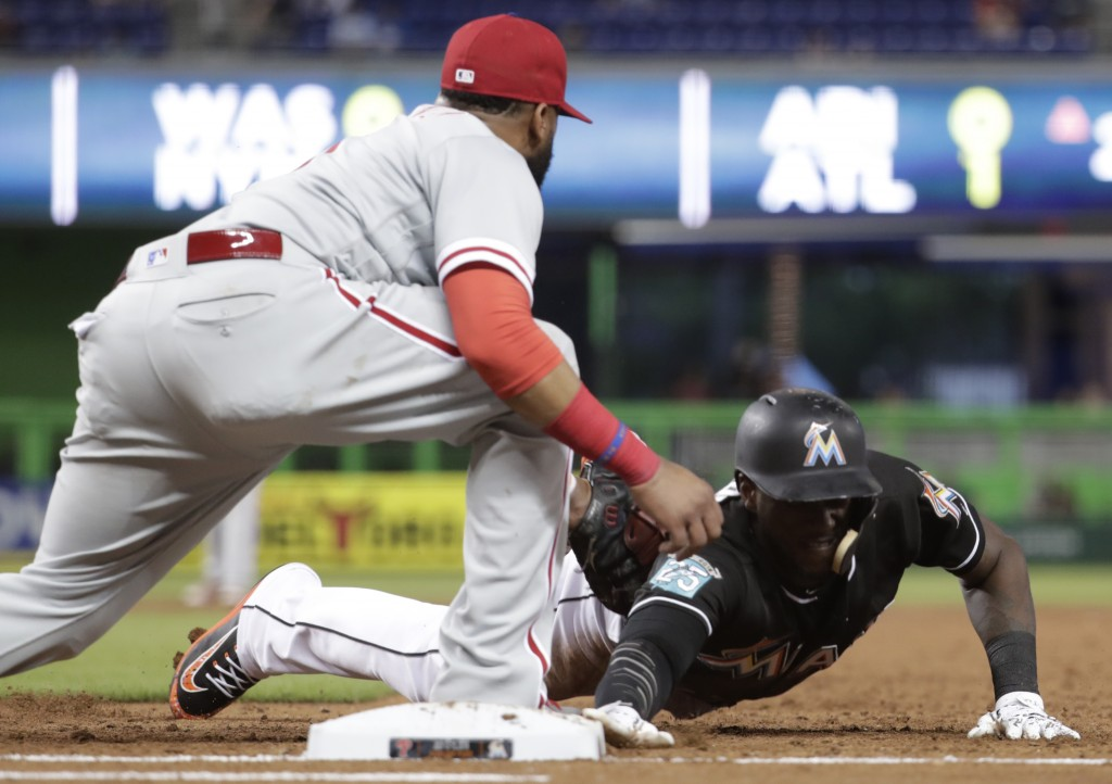 Miami Marlins' Cameron Maybin is picked off at first base as Philadelphia Phillies first baseman Carlos Santana makes the tag during the third inning