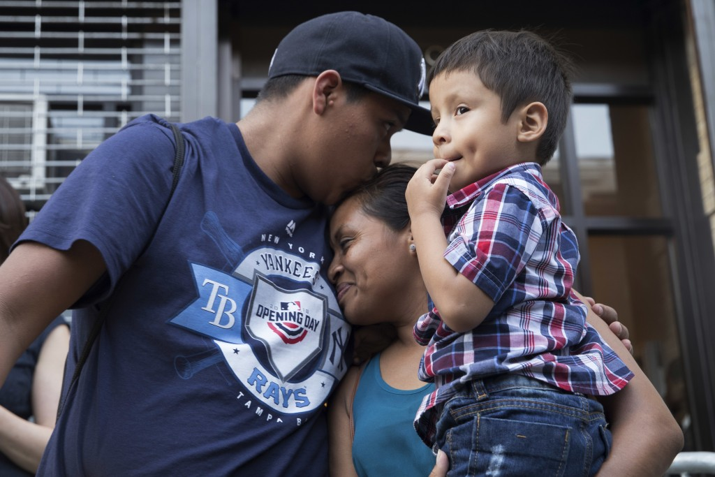 Rosayra Pablo Cruz, center, holds her son 5-year-old Fernando, right, as her 15-year-old Jordy kisses her outside the Cayuga Center, Friday, July 13,