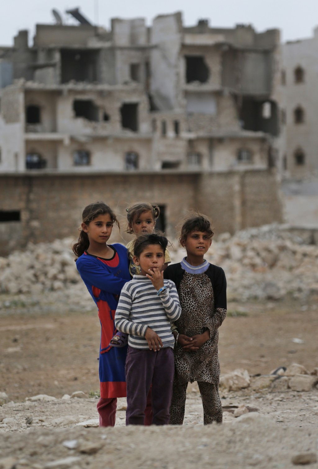 In this Tuesday, May 29, 2018, photo,  children stand in the outskirts of al-Bab, northern Syria. Nearly half of Syria's pre-war population of 23 mill