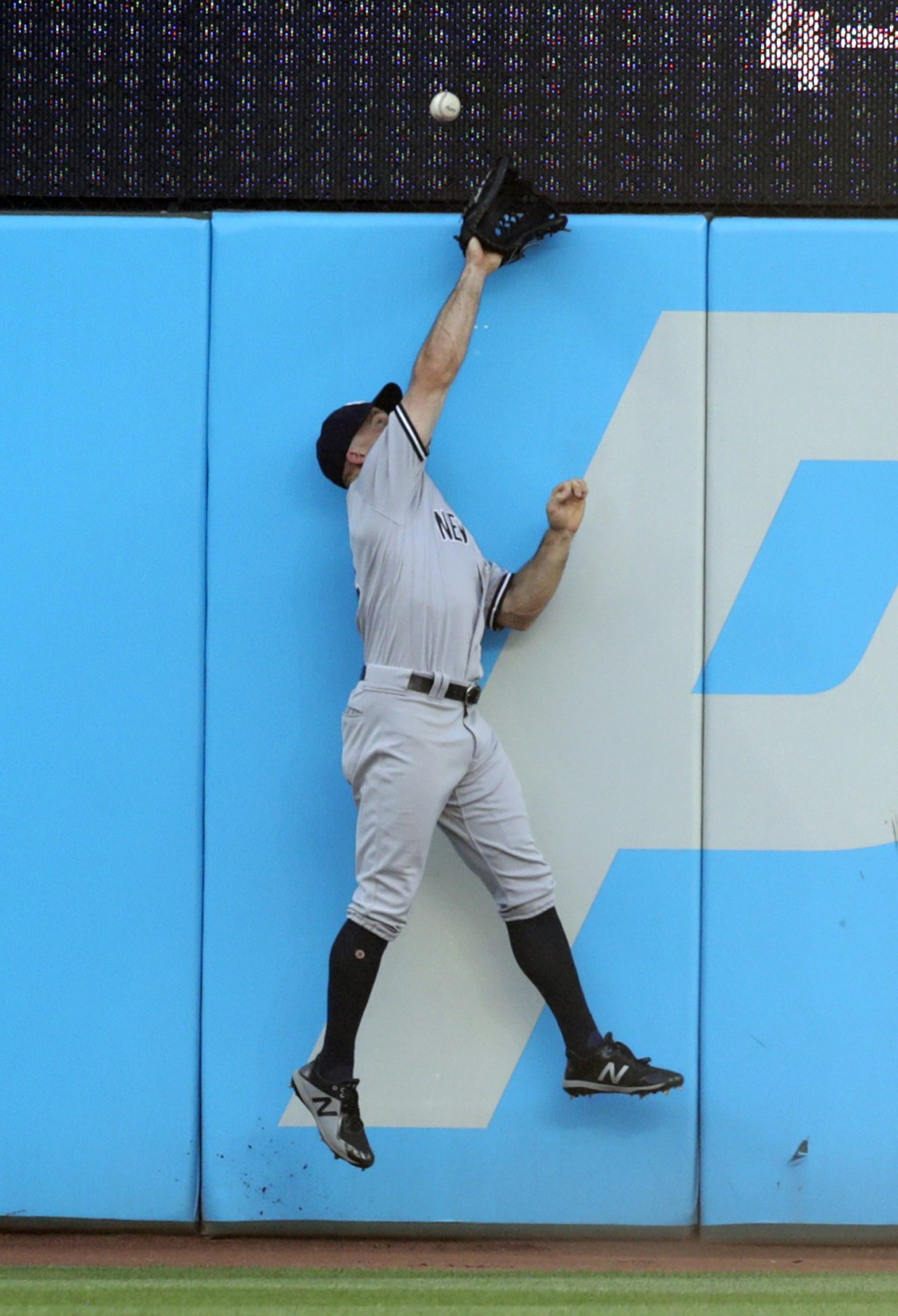 New York Yankees' Brett Gardner jumps at the wall but can't catch an RBI double by Cleveland Indians' Yan Gomes during the second inning of a baseball