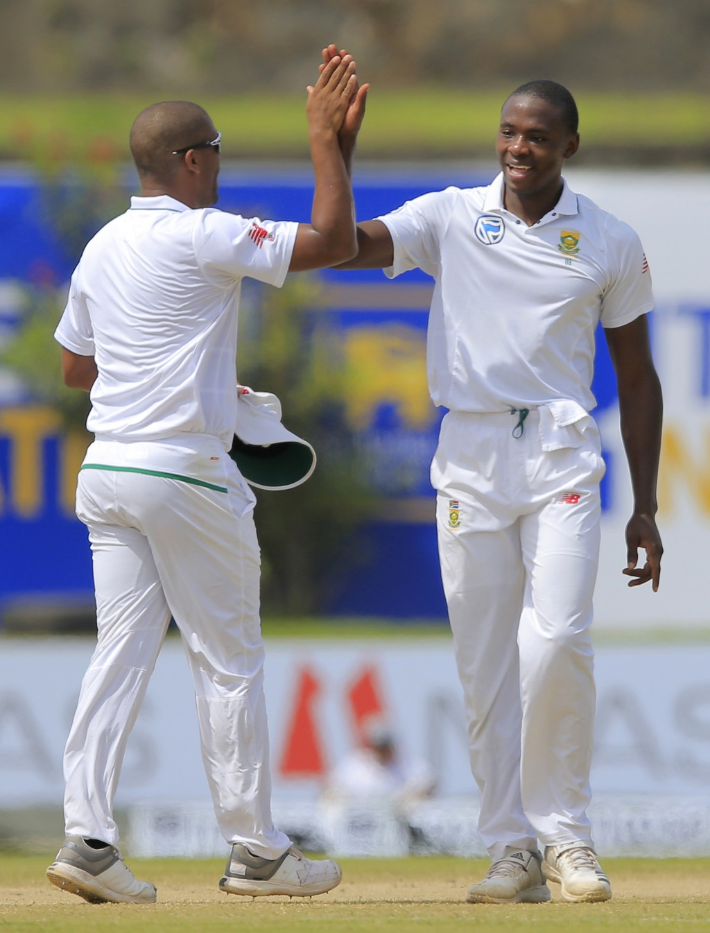 South Africa's Kagiso Rabada, right, celebrates with teammate Vernon Philander the dismissal of Sri Lanka's Niroshan Dickwella during the third day's