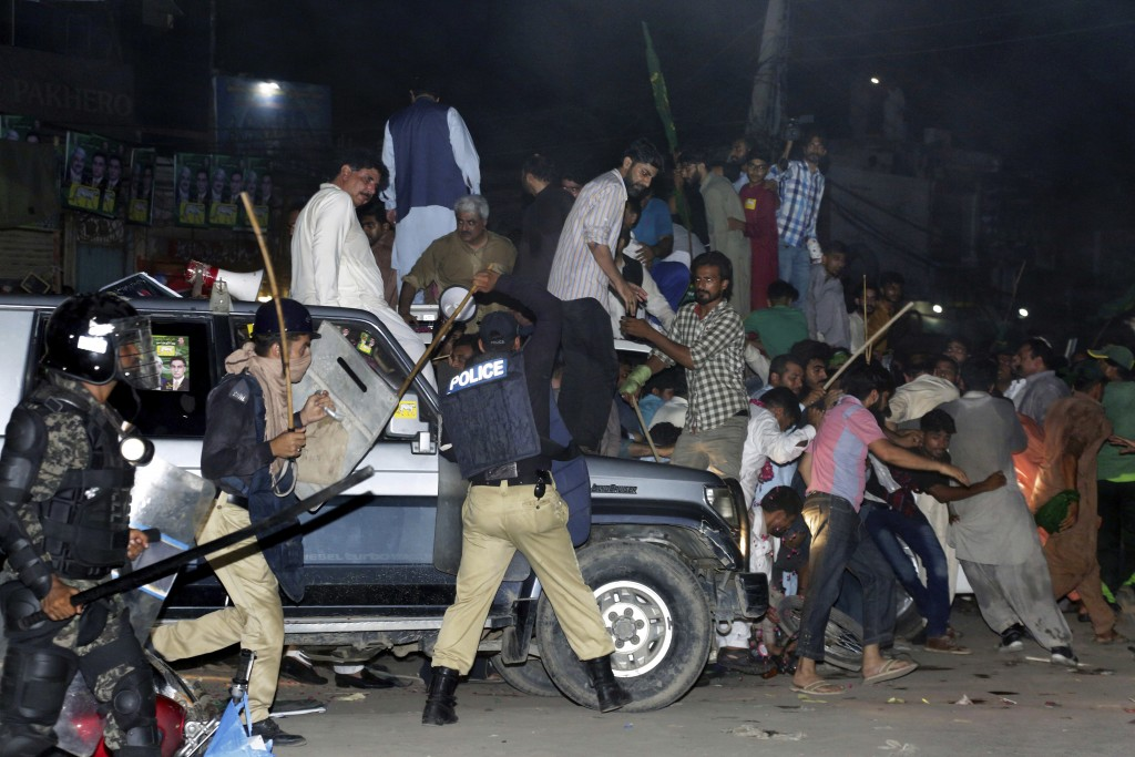 Police use force to disperse supporters of former prime minister Nawaz Sharif who gathered to see him in Lahore, Pakistan, Friday, July 13, 2018. Shar