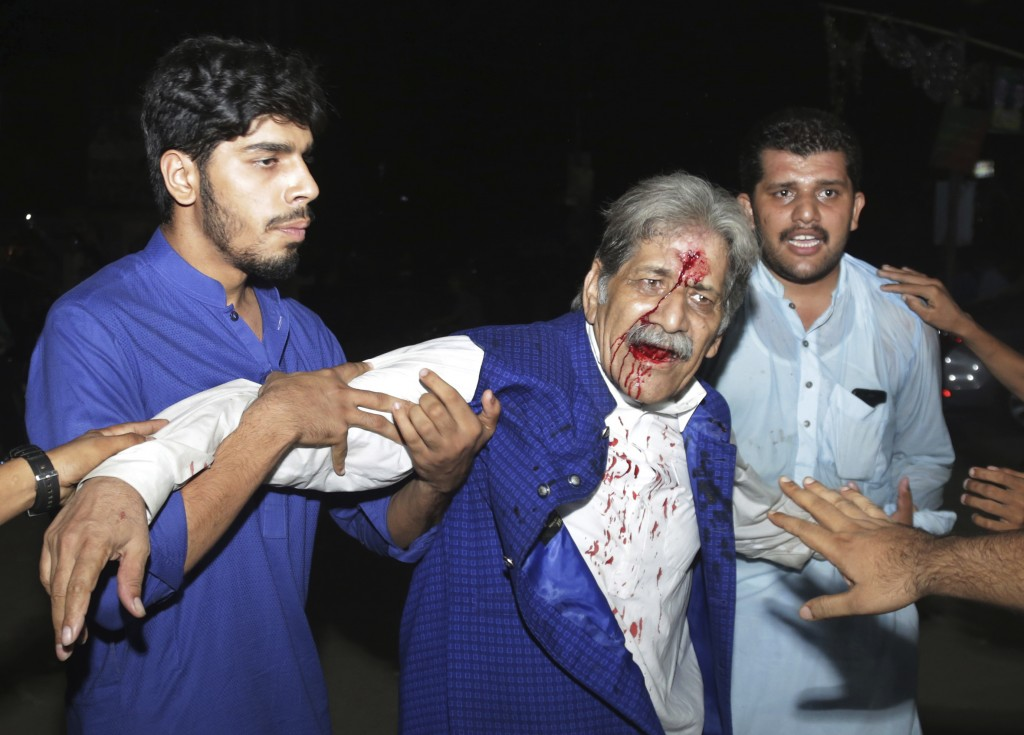 People hold an injured supporter of former prime minister Nawaz Sharif after a clash with police in Lahore, Pakistan, Friday, July 13, 2018. Sharif re