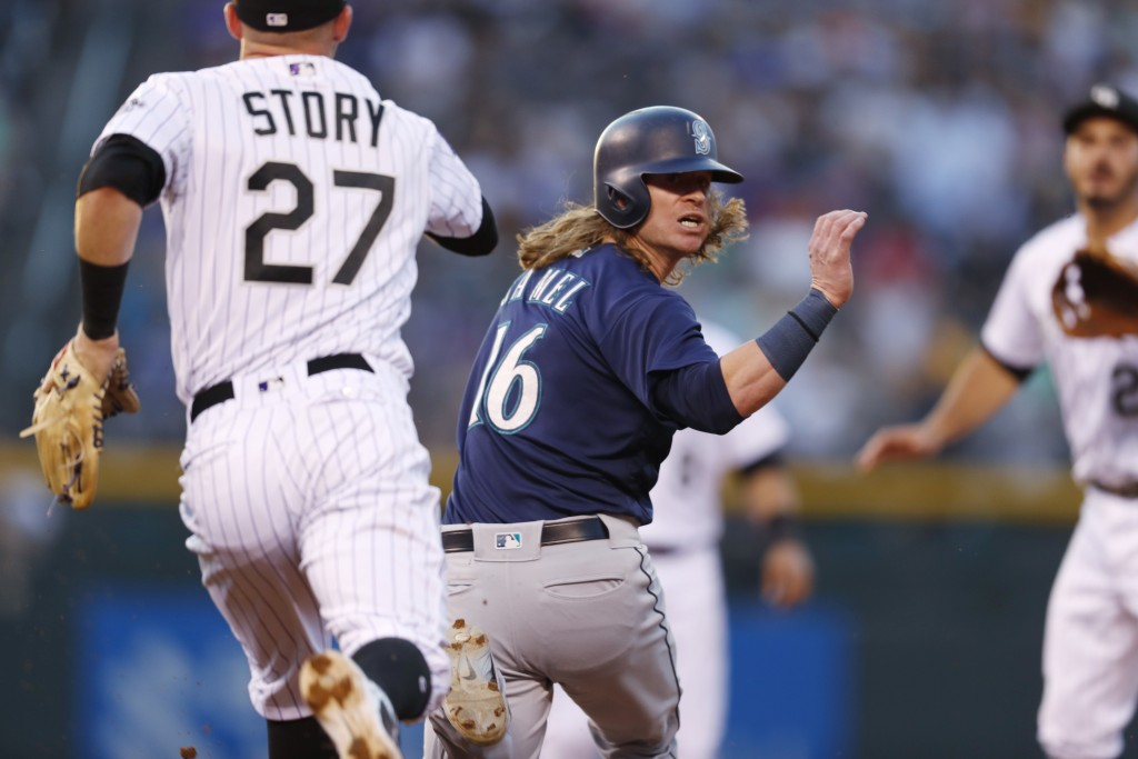 Seattle Mariners' Ben Gamel, center, gets caught in a rundown between first and second bases by Colorado Rockies shortstop Trevor Story, front, and th