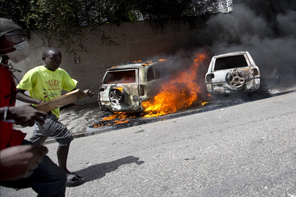 People run after cars were set on fire near the Best Western hotel during protests over a fuel price increase in Port-au-Prince, Haiti, on Saturday, J