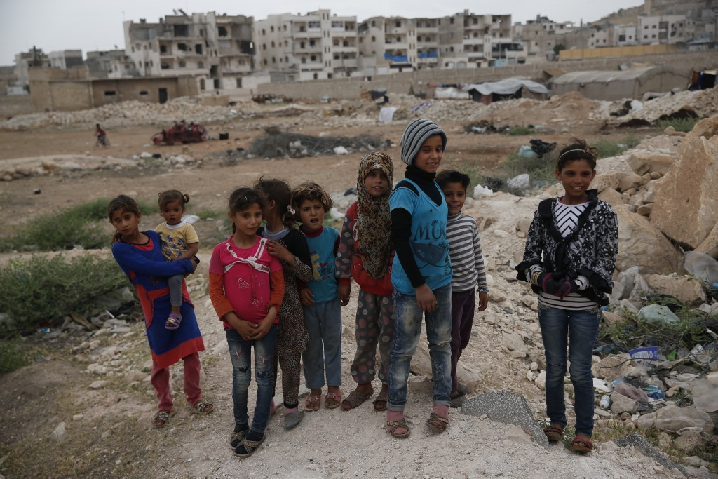 In this Tuesday, May 29, 2018, photo, children stand in the outskirts of al-Bab, northern Syria. Nearly half of Syria's pre-war population of 23 milli
