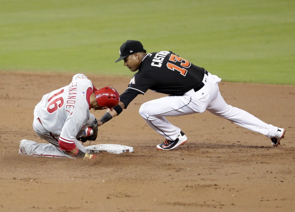 Philadelphia Phillies' Cesar Hernandez (16) is tagged out at second by Miami Marlins second baseman Starlin Castro during the third inning of a baseba