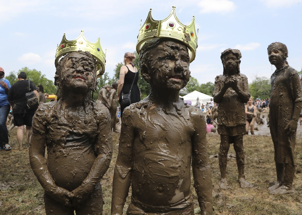 Molly Kofahl, 4, left, and Charles Daviskiba, 3, pose after being crowned Mud Day Queen and King during Mud Day at the Nankin Mills Park, Tuesday, Jul