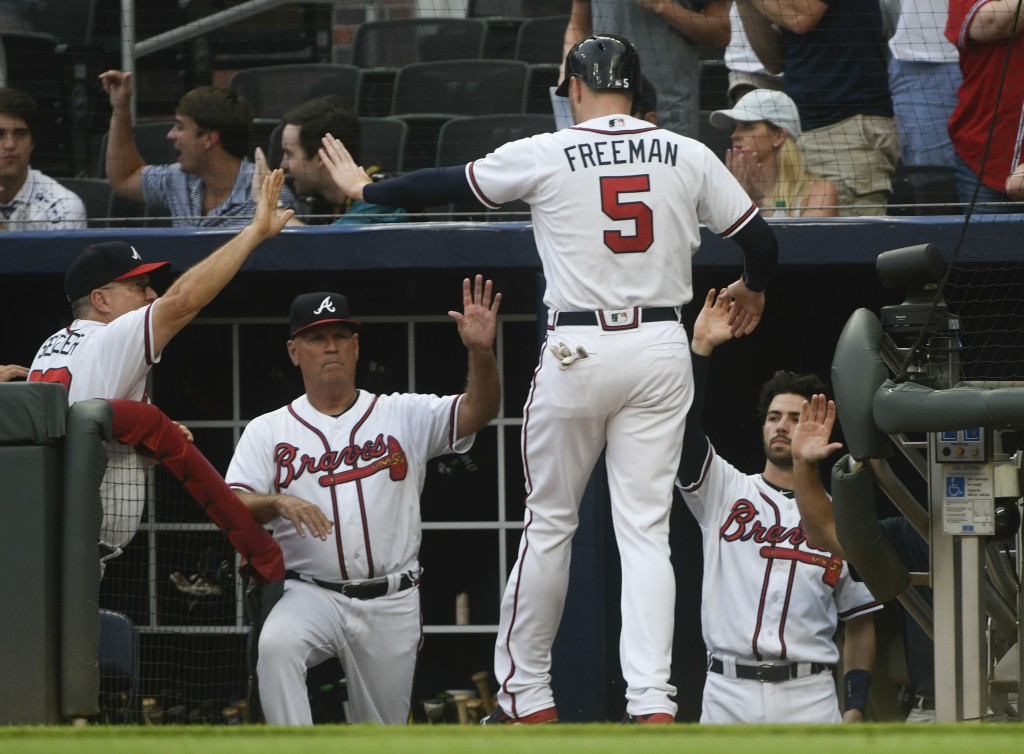 Atlanta Braves' Freddie Freeman enters the dugout after scoring against the Arizona Diamondbacks on single by Kurt Suzuki during the first inning of a