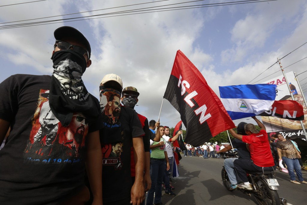 Sandinista supporters of President Daniel Ortega wait for his arrival in Masaya, Nicaragua, Friday, July 13, 2018. According to human rights groups, m
