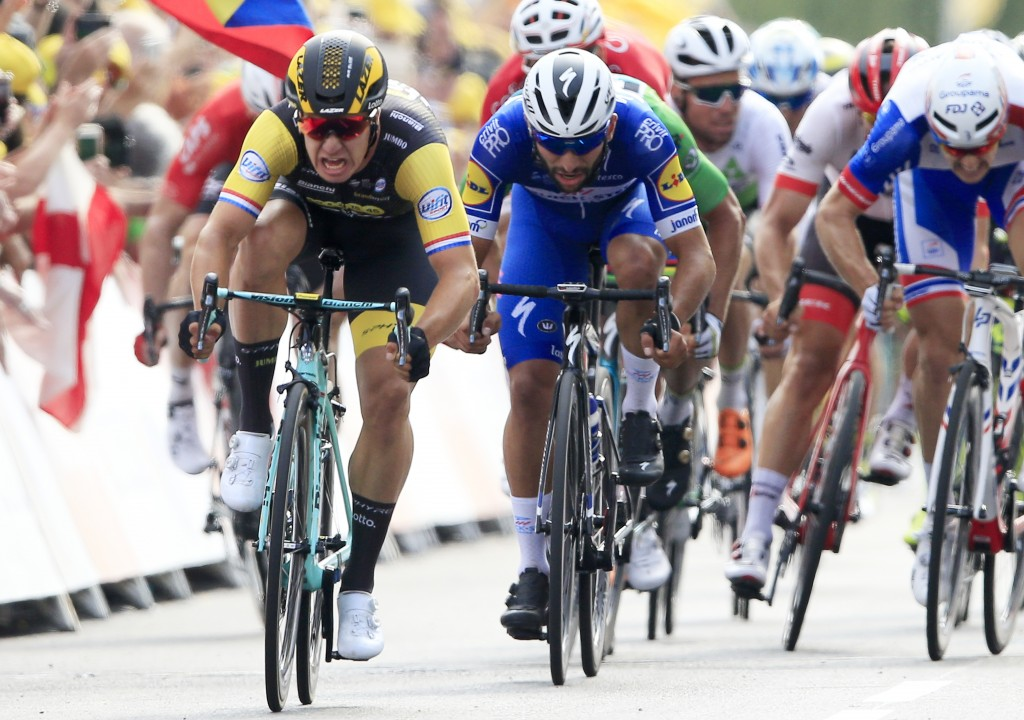 Netherlands' Dylan Groenewegen, left, crosses the finish line ahead of Colombia's Fernando Gaviria, center, to win the seventh stage of the Tour de Fr