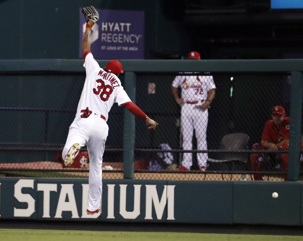 A double by Cincinnati Reds' Eugenio Suarez goes over the head of St. Louis Cardinals right fielder Jose Martinez during the fifth inning of a basebal
