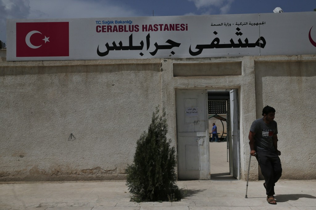 In this Wednesday, May 30, 2018, photo, a man leaves the hospital in Jarablus, northern Syria. Nearly half of Syria's pre-war population of 23 million