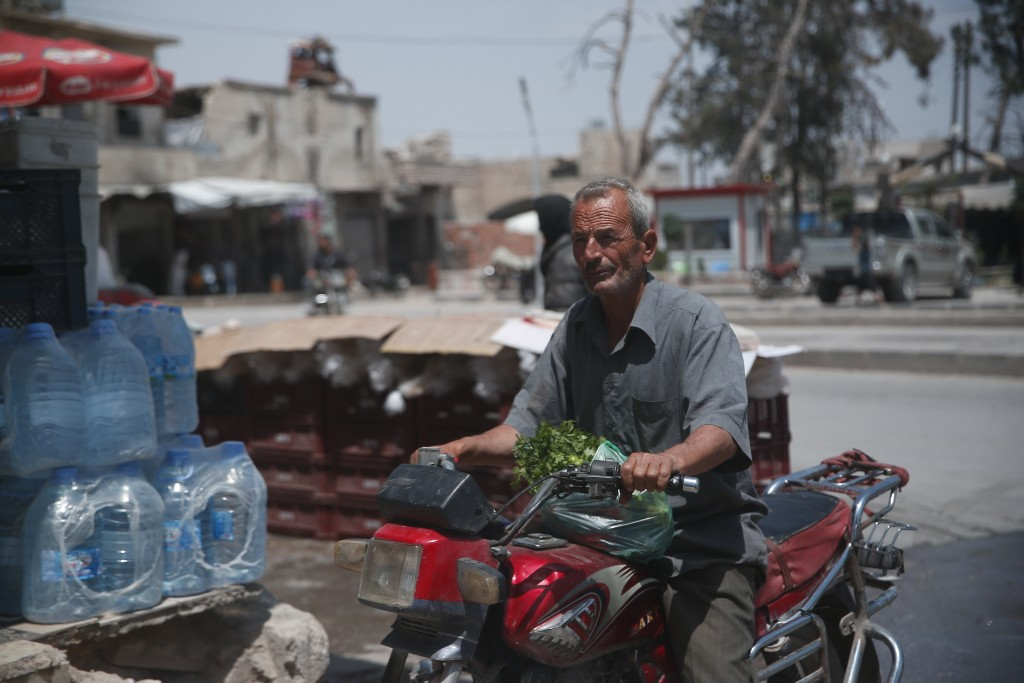 In this Tuesday, May 29, 2018, photo, a Syrian man drives his motorcycle in the centre of al-Bab, northern Syria. Nearly half of Syria's pre-war popul