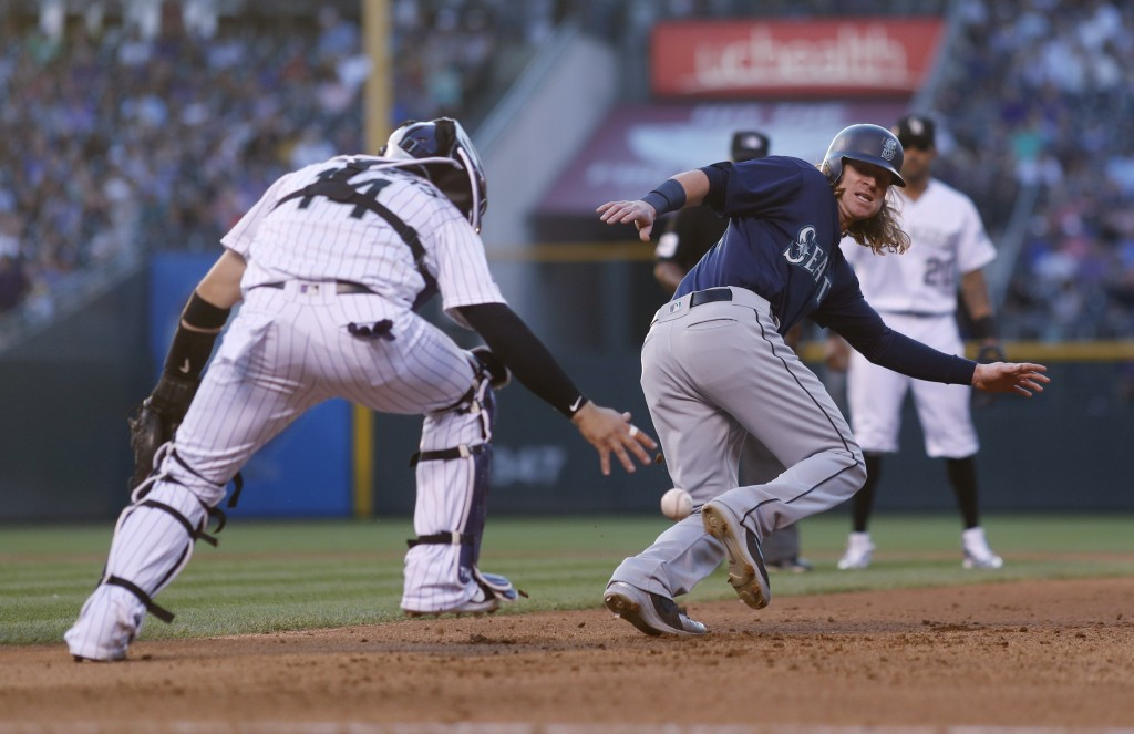 Colorado Rockies catcher Tony Wolters, front, drops the ball as he pursues Seattle Mariners' Ben Gamel in a rundown between first and second bases in