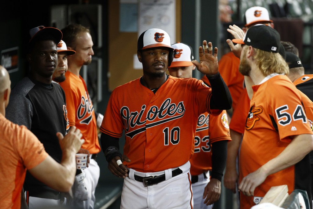 Baltimore Orioles' Adam Jones (10) high-fives teammates in the dugout after scoring on Danny Valencia's sacrifice fly ball in the fifth inning of a ba