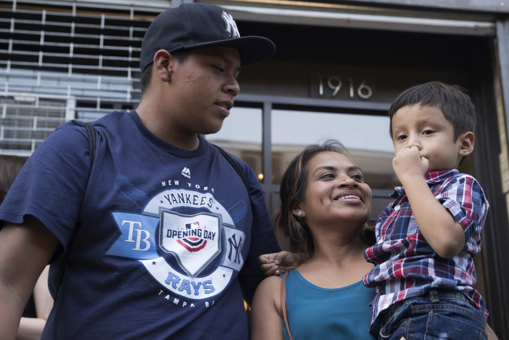 Rosayra Pablo Cruz, center, smiles at he sons 5-year-old Fernando, right, and 15-year-old Jordy outside the Cayuga Center, Friday, July 13, 2018, in N
