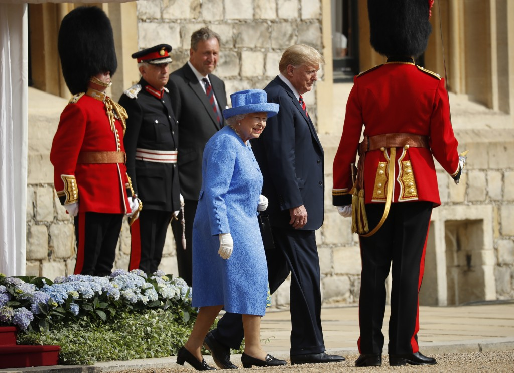 Queen Elizabeth II and President Donald Trump walk together to inspect the Guard of Honour at Windsor Castle in Windsor, England, Friday, July 13, 201