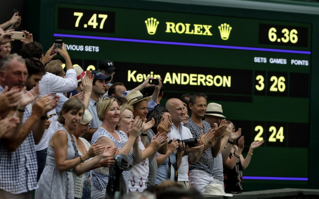 Spectators applaud as the scoreboard displays the final score in the men's singles semifinals match in which John Isner of the United States was defea
