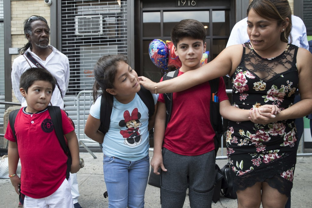 Yeni Gonzalez, right, stands with her children Lester, 11, second from right, and Jemelin, 9, second from left, and Deyuin, 6, during a news conferenc