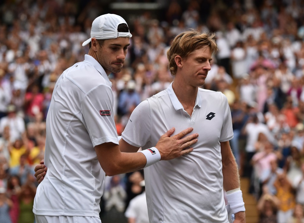 Kevin Anderson of South Africa, right, meets John Isner of the US on the court after defeating him in their men's singles semifinal match at the Wimbl