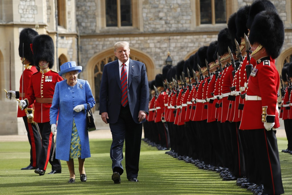 U.S. President Donald Trump with Queen Elizabeth II, inspects the Guard of Honour at Windsor Castle in Windsor, England, Friday, July 13, 2018. (AP Ph