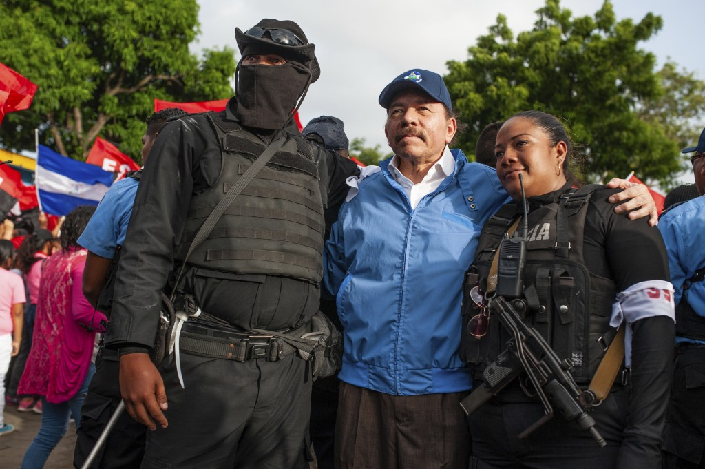 Nicaraguan police have their picture taken with President Daniel Ortega, in Masaya, Nicaragua, Friday, July 13, 2018. According to human rights groups