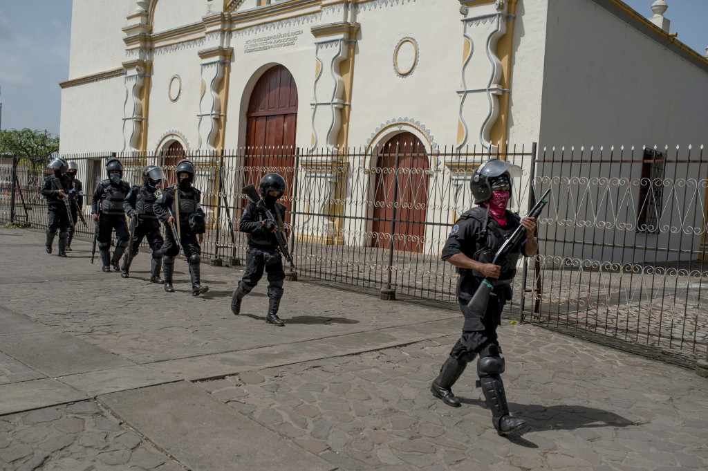 Heavily armed Nicaraguan police take positions before the arrival of President Daniel Ortega, in Masaya, Nicaragua, Friday, July 13, 2018. According t