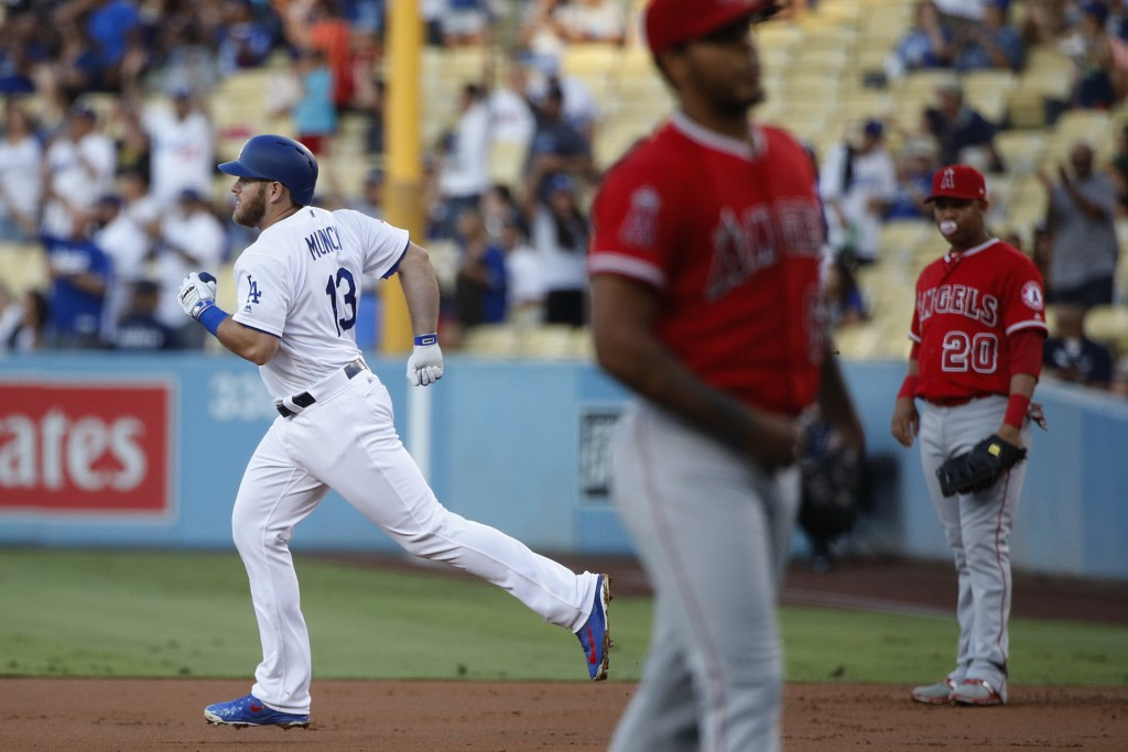 Los Angeles Dodgers' Max Muncy, left, rounds the bases after hitting a home run against Los Angeles Angels starting pitcher Felix Pena during the firs