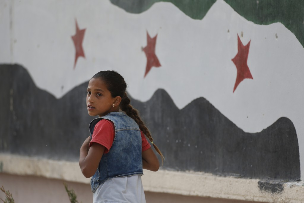 In this Wednesday, May 30, 2018, photo, a Syrian girl walks past a hospital in Jarablus, northern Syria. Nearly half of Syria's pre-war population of
