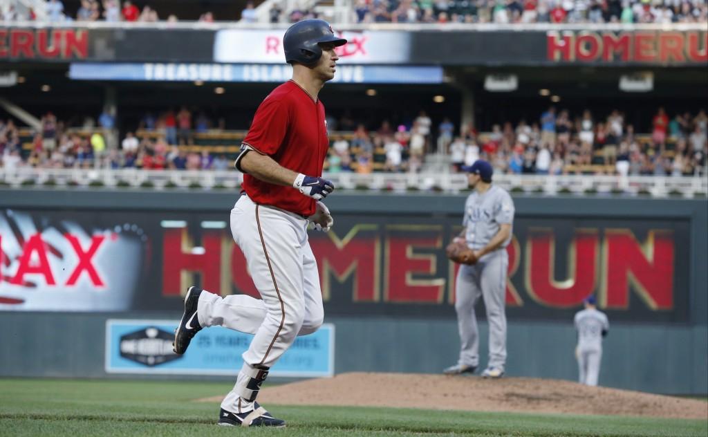 Minnesota Twins' Joe Mauer jogs home on a three-run home run off Tampa Bay Ray pitcher Nathan Eovaldi, right, during the third inning of a baseball ga