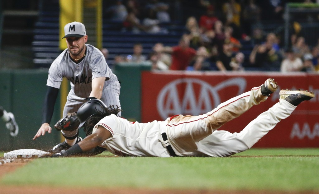 Pittsburgh Pirates' Josh Bell, right, dives in safely with a triple as Milwaukee Brewers third baseman Travis Shaw applies a late tag during the eight