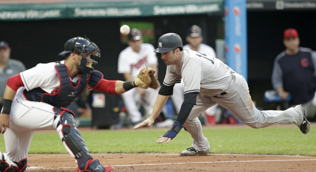 New York Yankees' Neil Walker, right, scores as Cleveland Indians' Yan Gomes can't hold on to the ball during the fifth inning of a baseball game Frid