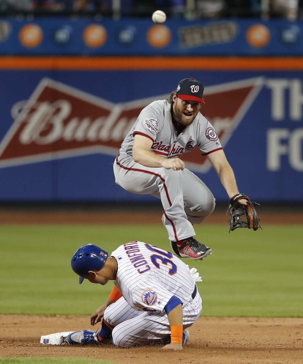 New York Mets' Michael Conforto (30) breaks up a double play as Washington Nationals second baseman Daniel Murphy makes the throw to first during the