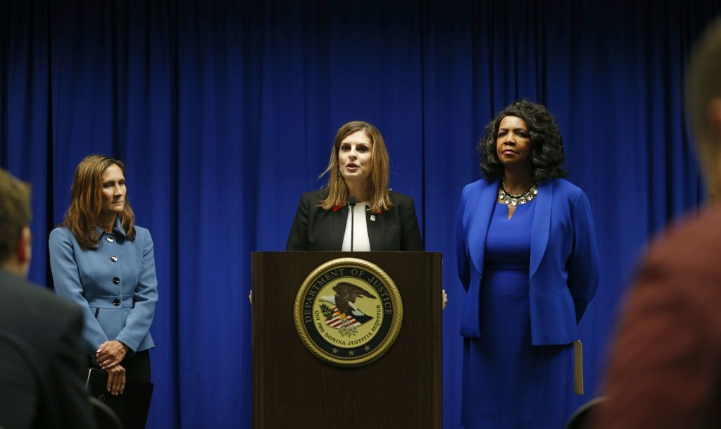 U.S. Attorney Erin Nealy Cox, center, holds a news conference on Friday, July 13, 2018 in Dallas.  Federal prosecutors say eight MS-13 members have be