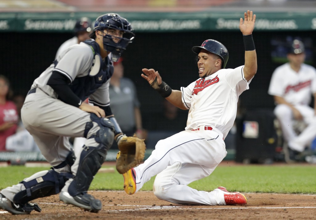Cleveland Indians' Michael Brantley scores as New York Yankees' Kyle Higashioka waits for the ball during the fifth inning of a baseball game Friday,