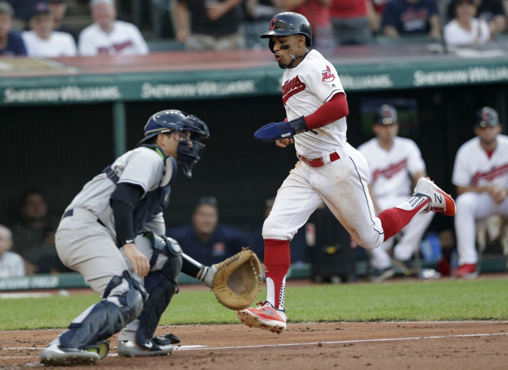 Cleveland Indians' Francisco Lindor, right, scores as New York Yankees' Kyle Higashioka waits for the throw  during the second inning of a baseball ga