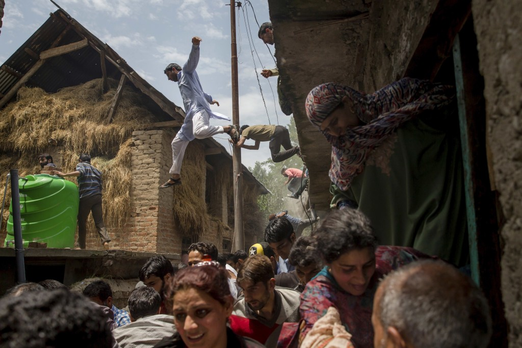 Kashmiri villagers inspecting a house damaged in a gun battle flee from it after hearing rumors of Indian army soldiers returning back to the site, wh