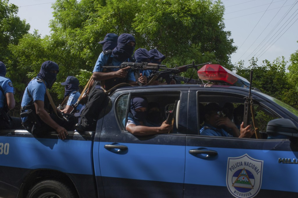 Heavily armed Nicaraguan police ride a pick up truck before the arrival of President Daniel Ortega, in Masaya, Nicaragua, Friday, July 13, 2018. Accor