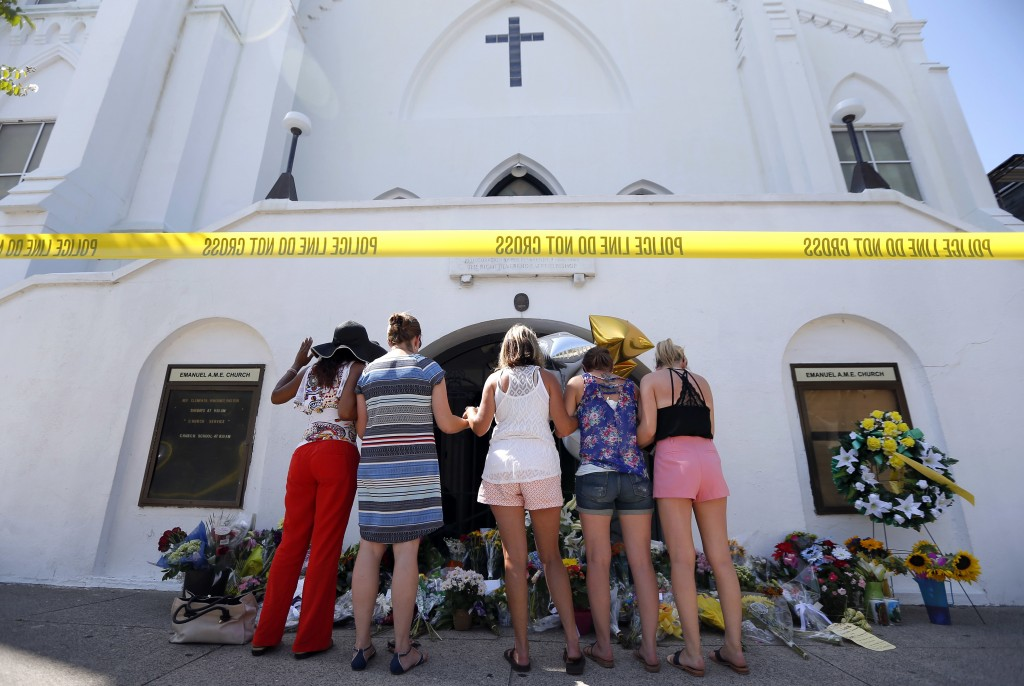 FILE - In this June 18, 2015, file photo, a group of women pray together at a makeshift memorial on the sidewalk in front of the Emanuel AME Church in...